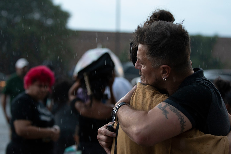 David Flores, left, is embraced in the rain at the vigil for Sincere Ash at Lane Tech College Prep on August 9, 2018 in Chicago, IL.   Colin Boyle/Sun-Times