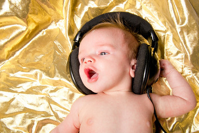 Baby boy on gold background sings along with music from headphones