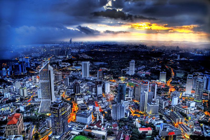 """<h2>Sunset Storm over Kuala Lumpur</h2> <br/>A series of violent storms came through Kuala Lumpur, allowing a few surreal shots of the city. It went from very dark and cloud to torrential downpour to beautiful sunset. It reminded me of the storms on the plains of Texas.<br/><br/>Kuala Lumpur is a very interesting city and is quite unique in Asia. I'd love to get up on top of those Petronas Towers there to take some shots, but I look like a suspicious white guy with my huge backpack. They tell me all white people look alike. …and smell like wet puppies.<br/><br/>- Trey Ratcliff<br/><br/><a href=""""http://www.stuckincustoms.com/2007/01/30/storm-hitting-kuala-lumpur/"""" rel=""""nofollow"""">Click here to read the rest of this post at the Stuck in Customs blog.</a>"""