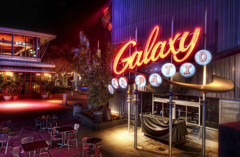 """<h2>The Galaxy Cafe</h2> <br/>When I was recently at Universal Orlando, Ethan and I made a late night getaway to do some exploration.  We were staying at the Portofino, and they have a wonderful boat system that skirts you down to the main park.  We jumped on the boat after dark to go down and visit this little area of shops, restaurants, and dozens of other interesting things to see and experience.  I've gotten him used to the idea of roaming aimlessly, taking photos of this and that, with no real goal other than exploration and noticing little things.<br/><br/>Ethan and I stopped at a tiny trinket store and bought a few necklaces and bracelets for ourselves and the girls.  After that, we grabbed a few hot cocoas, got on the boat, and drifted back home.  We took our time, drank our hot cocoas, and helped each other put on our bracelets.<br/><br/>- Trey Ratcliff<br/><br/><a href=""""http://www.stuckincustoms.com/2010/05/11/the-galaxy-cafe/"""" rel=""""nofollow"""">Click here to read the rest of this post at the Stuck in Customs blog.</a>"""