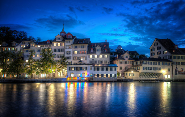 Zurich at Night It was a cool night -- one of those nights when I was glad I lugged around a jacket all day.    These dark waters that run through old European cities at night set an interesting mood.  I can't quite put my finger on it...  heavy and deep and dark... but strange and light and reflective on top.  I think some of these things you can't quite see end up in the photo, somehow.  - Trey Ratcliff  Read the rest here at the Stuck in Customs blog.