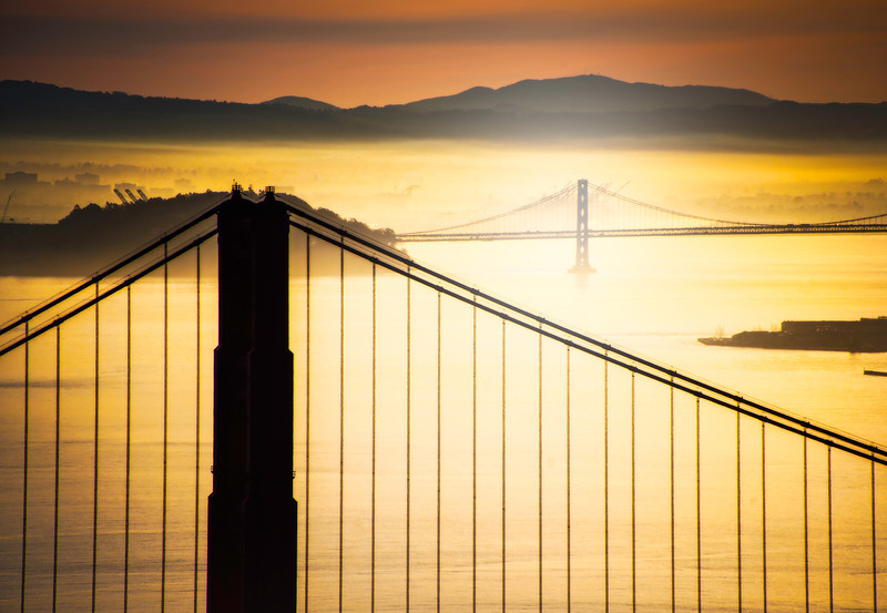 "<h2>Sunrise over San Francisco Bay</h2> After my very early morning in San Francisco, I started moving my way further up the mountain.  The orientation of the bridges kept changing relative to one another with Oakland in the background.  Once I got up high enough, I affixed the 28-300mm to the body, zoomed in, and got this shot.<br/><br/>I was lucky that the morning mist/fog gave a nice sheen to everything.  I kind of wish I lived in SF.  I think I would force myself to get up here every day for a year... and see the different light every single day.<br/><br/>- Trey Ratcliff<br/><br/><a href=""http://www.stuckincustoms.com/2012/04/08/sunrise-over-san-francisco-bay/"" rel=""nofollow"">Read the rest of this post at the Stuck in Customs blog.</a>"