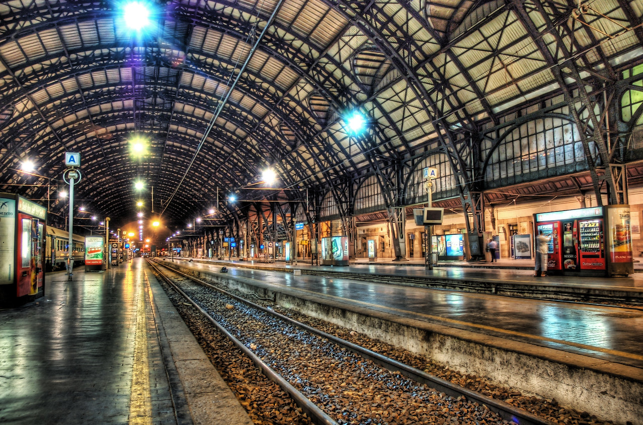 "Milan Train Station at Midnight If you want to see how I made this (and how you can too!), visit my HDR Tutorial. I hope it gives you some new tricks!I had a super-long day in Milan. I was tired and just wanted to go back to the hotel to have a cappuccino in the bar and edit photography on my laptop. But I remembered the really pretty train station and how I wanted to get a shot with nobody around.I went in around midnight, found the perfect spot, and then shot away.The HDR process always takes that slick concrete and makes it extra-reflective. Reflective ground is always great for photography. Also, people always think that I ""colored"" the lights up at the top, but I did not. In fact, I never ""paint"" on my photos. Any color that you see in them was actually there, except in the cases when I apply a texture treatment.- Trey RatcliffClick here to read the rest of this post at the Stuck in Customs blog."