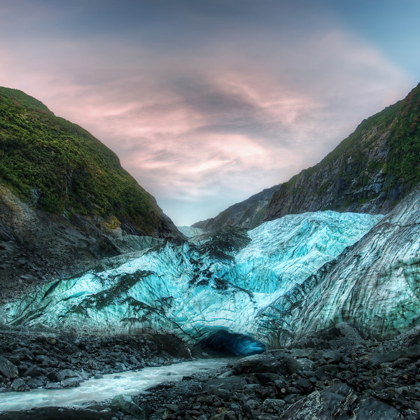 """The Icy Cave at the Franz Josef Glacier I've had an amazing time so far in New Zealand.  I'm here for about a month with my family.  On a recent evening, my 8-year-old son and I went on a decent hike to the base of the Franz Josef Glacier on towards the west coast of the southern island.  Once we got close to it, we could see the icy blue cave where a glacial-white river emerged.  Awesome!  My son looked at me and said, """"Wow.  I feel like we just discovered Atlantis!""""In truth, we stayed way too late.  This was a good 1.5 km from the car, and it was pretty dark.  By the time we got back, it was totally dark except for the moonlight that helped guide us home.  I had a flashlight hanging off my camera """"just in case"""", but, as case would have it, the flashlight fell off into the glacial river!- Trey RatcliffClick here to read the rest of this post at the Stuck in Customs blog."""