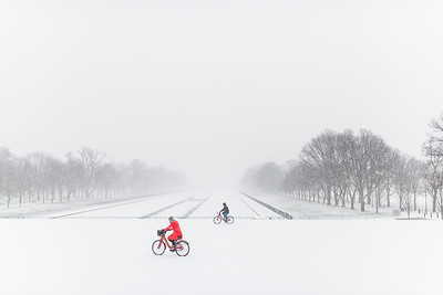 Two cyclists brave the snow and ride their bicycles across the Lincoln Memoral on Jan. 22, 2016.