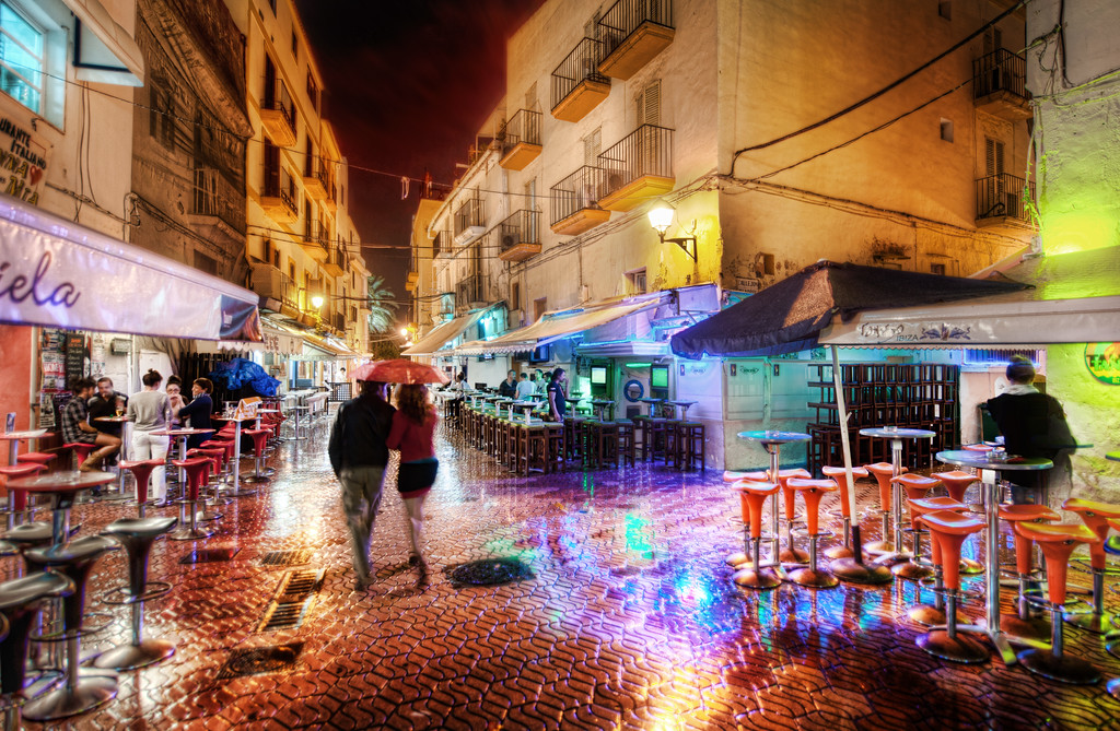 A Rainy and Romantic Night in Ibiza Part of Ibiza is an old walled medieval town that is surrounded by layers of winding streets old shops intermixed with homes.  A few streets away from the walls, some of the streets are full of pubs and quirky shops...  I think it's better to explore them at night than in the day -- and especially so in the rain.On this night, it was a little chilly and rainy, but that does not effect my camera.  I've never had a problem because of rain or cold or heat or anything.  It just works!The rainy streets were full of colors and life.  I saw this couple quickly walking under an umbrella so I took a quick one to capture the scene. - Trey RatcliffClick here to read the rest of this post at the Stuck in Customs blog.