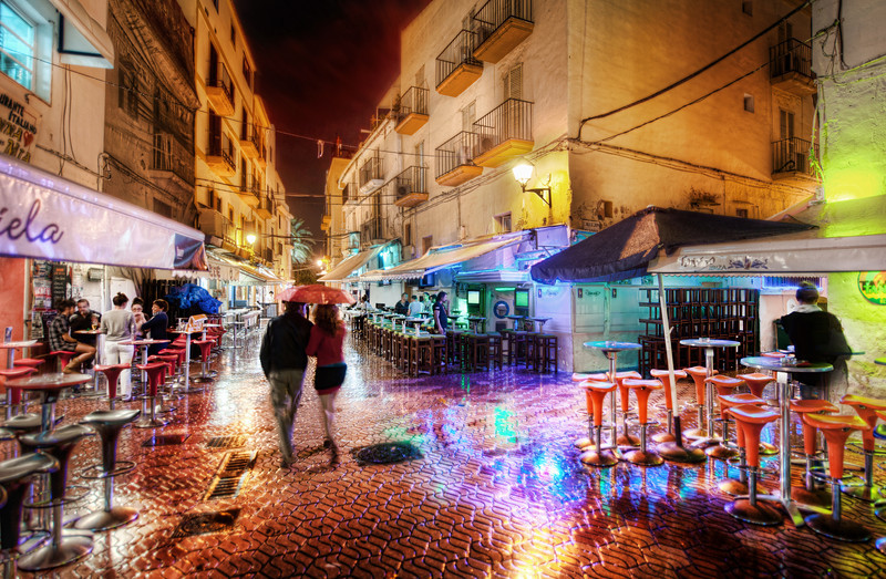 "<h2> A Rainy and Romantic Night in Ibiza</h2> <br/>Part of Ibiza is an old walled medieval town that is surrounded by layers of winding streets old shops intermixed with homes.  A few streets away from the walls, some of the streets are full of pubs and quirky shops...  I think it's better to explore them at night than in the day -- and especially so in the rain.<br/><br/>On this night, it was a little chilly and rainy, but that does not effect my camera.  I've never had a problem because of rain or cold or heat or <em>anything</em>.  It just works!<br/><br/>The rainy streets were full of colors and life.  I saw this couple quickly walking under an umbrella so I took a quick one to capture the scene. <br/><br/>- Trey Ratcliff<br/><br/><a href=""http://www.stuckincustoms.com/2011/02/07/a-rainy-and-romantic-night-in-ibiza/"" rel=""nofollow"">Click here to read the rest of this post at the Stuck in Customs blog.</a>"