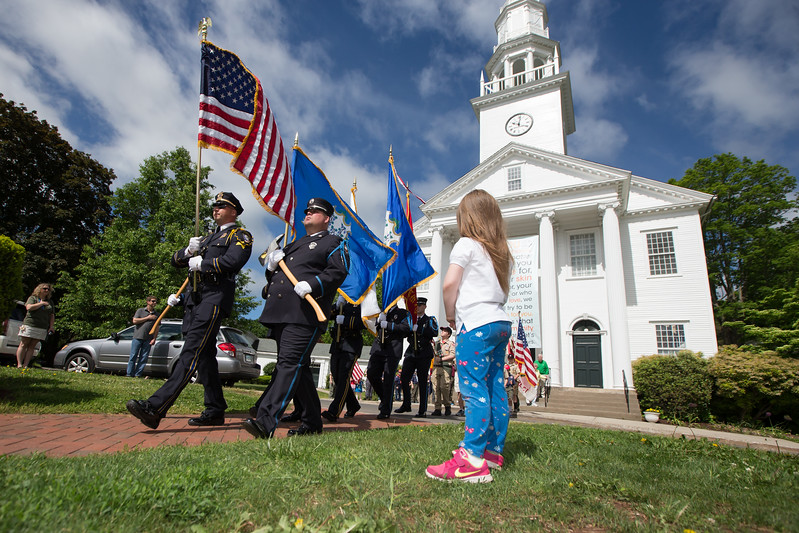 Mackenzie Sirois 6 of Cheshire watches as the Cheshire Police and Fire color guard present the American flag to start precedings Saturday during the Cheshire Memorial Day Ceremony at the Cheshire Town Green in Cheshire. May. 27, 2017 | Justin Weekes / For the Record-Journal