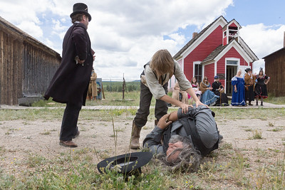 1800's reenactment actors playing the part of a gunfighter dying in the street with a boy encouraging him to get up while the undertaker waits to do his job and the towns people look on in the background.