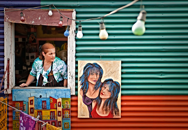 "The Artist Takes a Break In Buenos Aires, there is a very artsy area called La Boca.  It's filled with tiny little studios, restaurants, tango in the streets, and all kinds of life.  The colors are bright and vibrant, so, of course, I went crazy with my camera there.  While exploring, I found this cool artist's studio on the second floor of an interior section.  I had on my 24-70mm, and I was admiring her studio at f2.4.  Then, by luck, she came to the window to peer out.  I grabbed a quick one.This was edited with Nik Software, so I took this opportunity to write a Nik Review for y'all!  It's very cool software, and I have put a bunch of new images inside of there...  Many of them are ""in progress"", and might not show up in their final form on the blog for a few weeks.- Trey RatcliffClick here to read the rest of this post at the Stuck in Customs blog."