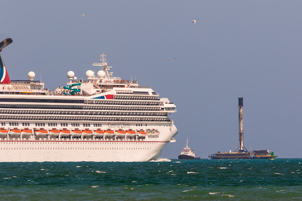 The SpaceX Falcon 9 being returned to port just days after landing at sea, passing by a Carnival Liberty cruiseliner.