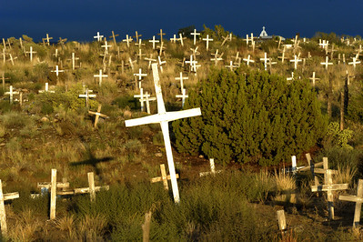 Navajo Mission Cemetery, Farmington NM at sunset after a thunderstorm.  Most of these graves are unmarked except for the crosses and date to the early 1900's.