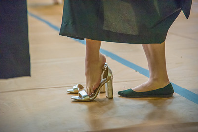A graduate changes into high heels prior to a commencement ceremony at Moby Arena on May 11, 2018.  Almost 140 graduates received doctorates from the College of Veterinary Medicine and Biomedical Sciences.