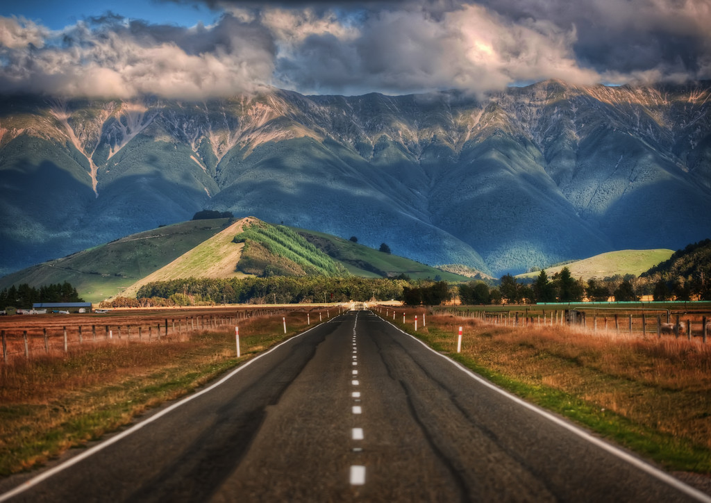 """The Long Road to New Zealand This is one of countless beautiful roads that crisscross New Zealand.  I'm afraid I've forgotten exactly where I was when I took this photo!   I know that is very lame, but I bet people around here can help me pinpoint the area.As far as the camera settings, this is the kind of shot you can get with something called """"compression,"""" a method where you use a zoom lens and zoom in quite far.  It takes images in the distance and makes them larger than life.- Trey RatcliffRead more here at the Stuck in Customs blog."""