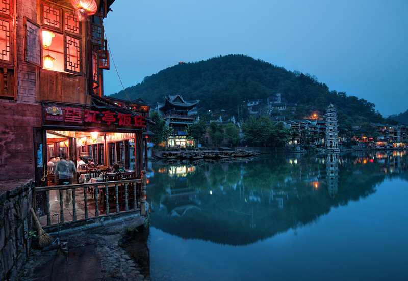 """<h2>Night Settles In Feung Huang</h2> There is a general poetic peace when it begins to go dark outside and the town comes alight with shopkeepers and villagers come out to turn on the lights.  If you look around, you can see them popping on, one at a time, like little fireflies coming out to play for the evening.  This area is no different, and it's made even more magical by the little river that flows through the middle of it all.  And then you are faced with all these nice decisions... where to eat?  where to drink?  where to find an inn for the night?    - Trey Ratcliff  Read more <a href=""""http://www.stuckincustoms.com/2011/06/30/night-settles-in-feung-huang/"""">here</a> at the Stuck in Customs blog."""
