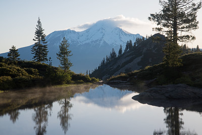 Mount Shasta reflects in the still calm waters of a quiet lake in northern California.