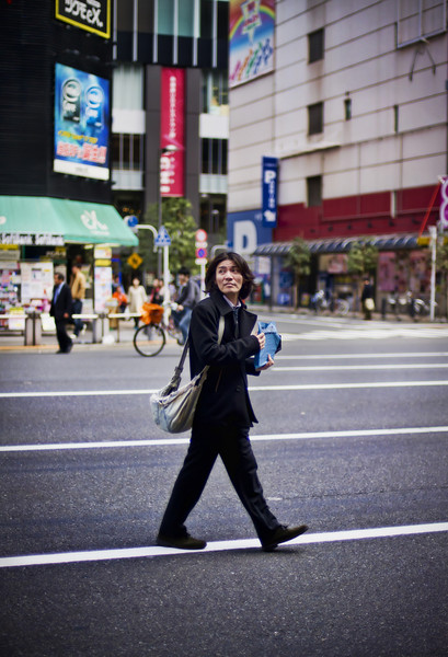 """<h2>Man Crossing Street</h2> <br/>I spent a lot of time in this dynamic area of Tokyo.  It's sort of the techno-nerd electronic center of the Japanese world.  So I felt right at home there with my fellow nerds.  But this guy certainly stood out.  He was crossing the street and looking extremely Japo-cool.  I pulled up my 50mm and waited for the time to feel right before I snapped the photo.  Afterward, of course, it is kind of fun to look at little bits of the photo and find out, compositionally, why the photo did indeed feel """"right"""" to take at that moment.<br/><br/>- Trey Ratcliff<br/><br/><a href=""""http://www.stuckincustoms.com/2010/10/13/man-crossing-street/"""" rel=""""nofollow"""">Click here to read the rest of this post at the Stuck in Customs blog.</a>"""