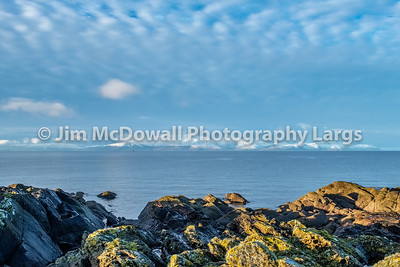 Snow Covered Arran and Lichen Covered Rocks on the Portencross Foreshore.