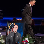 Colorado Governor John Hickenlooper walks off the stage past a picture of El Paso County Sheriff's deputy Micah Flick after speaking at Flick's memorial service at New Life Church in Colorado Springs, Colo. on Saturday, February 10, 2018.<br /> <br /> (Nadav Soroker, The Gazette)