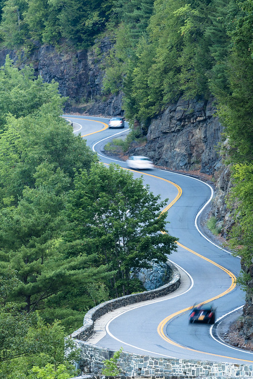 Three cars traveling on scenic Hawk's Nest winding road
