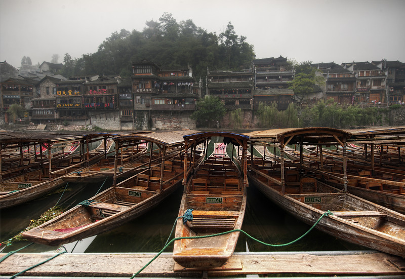 "<h2>Boats in Ancient China</h2> <br/>This is the spot where I cracked a rib.  I'll tell that story in a moment...  This is the ancient village of Feng Huang in distant southern China.  I hired a local driver to get me there, and the ride was longer than most plane trips!  And a lot less comfortable...  Anyway, after arriving, I had a wonderful time exploring.  One morning, the old town was covered with thick fog.  And it's that still, wet, timeless fog of China.  When you are looking at it, you become convinced it will just never go away.  I worked my way down one of the banks to an area where the local rivermen keep the boats to grab this shot.  The morning was wet, obviously, and that was the downfall of my mishap.  I stepped down onto what looked like damp, dirty concrete.  I've done this a thousand times.  I was carrying my D3X with 14-24mm lens on a tripod on my left hand and holding my D3S with 50mm 1.4 prime in my right hand.  It turned out that I was stepping onto that super-slick wet clay.  It was razor-thin and slicker than ice.  I didn't stand a chance.  I fell right down, both cameras slamming into the ground.  The D3X hit extra hard because the tripod gave it some painful torque.  I landed on the D3S, it's body caving in one of ribs... right in the middle of the man-nipple area.  It was too bad because I've always treasured that area.  I made reference to the injury when I was still unsure about it in this <a rel=""nofollow"" href=""http://www.youtube.com/stuckincustoms#p/u/9/VW1RzjWRDaQ"">Part 2 China Interview</a>.  <br/><br/>- Trey Ratcliff<br/><br/><a href=""http://www.stuckincustoms.com/2011/01/08/boats-in-ancient-china/"" rel=""nofollow"">Click here to read the rest of this post at the Stuck in Customs blog.</a>"