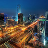 "<h2>Bustling Beijing</h2> <br/>Getting this photo was not easy at all!<br/><br/>I knew of this area of Beijing called the CBD, or Central Business District.  I notice that they have all these catchy names here, much like the building I took this photo from: ""China Merchants Building.""  At any rate, I had the driver circle the business district a few times so I could find a good angle.  We found one in this building, but did not know if we could take a photo from the top floor.  Woo went in first.  This might have been a mistake because during the shoot he admitted he had a dreadful fear of heights.  But he said it in such a charming British accent I thought it could have been my subconscious.<br/><br/>We went up to the 32nd floor.  No windows no dice.  We then went to the 31st floor, but the confused secretary would not let us through.  Then we tried 30.  The secretary said yes and let us into a boardroom, but the angle was not right and the other offices were busy.  So we went to 29.<br/><br/>The secretary on 29 was confused so I instructed Woo to tell her, firmly, ""We are with the Government.""<br/><br/>- Trey Ratcliff<br/><br/>Find out what happened <a href=""http://www.stuckincustoms.com/2010/10/10/bustling-beijing/"">here</a> at stuckincustoms.com."