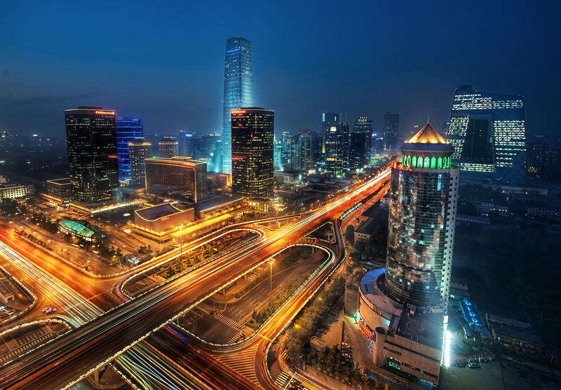 """<h2>Bustling Beijing</h2> <br/>Getting this photo was not easy at all!<br/><br/>I knew of this area of Beijing called the CBD, or Central Business District.  I notice that they have all these catchy names here, much like the building I took this photo from: """"China Merchants Building.""""  At any rate, I had the driver circle the business district a few times so I could find a good angle.  We found one in this building, but did not know if we could take a photo from the top floor.  Woo went in first.  This might have been a mistake because during the shoot he admitted he had a dreadful fear of heights.  But he said it in such a charming British accent I thought it could have been my subconscious.<br/><br/>We went up to the 32nd floor.  No windows no dice.  We then went to the 31st floor, but the confused secretary would not let us through.  Then we tried 30.  The secretary said yes and let us into a boardroom, but the angle was not right and the other offices were busy.  So we went to 29.<br/><br/>The secretary on 29 was confused so I instructed Woo to tell her, firmly, """"We are with the Government.""""<br/><br/>- Trey Ratcliff<br/><br/>Find out what happened <a href=""""http://www.stuckincustoms.com/2010/10/10/bustling-beijing/"""">here</a> at stuckincustoms.com."""