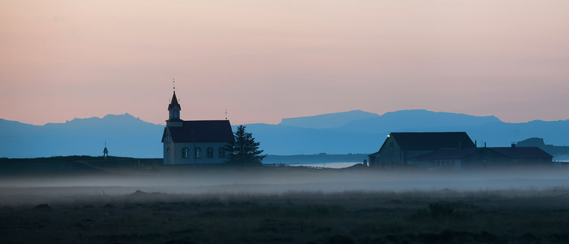 "<h2>Church in the Fog</h2> <br/>I was driving along the southern coast of Iceland on the way to Vik, and I started going throw an area of lowlands.  Around midnight or so, the sun was getting pretty low in the west, and it gave the sky a slight pink glow in almost every direction.<br/><br/>I shot this one at a 200mm at F/6.7.  I don't often take out my zooms for landscapes, but it does provide a nice compression that gives an unexpected feel to the final photo.  It's really hard to explain in words, but maybe you can sense of this framing in the final result.  It just can't be done with a wide-angle lens, even if I was a lot closer.<br/><br/>- Trey Ratcliff<br/><br/><a href=""http://www.stuckincustoms.com/2011/05/06/church-in-the-fog-and-interview-with-nikon/"" rel=""nofollow"">Click here to read the rest of this post at the Stuck in Customs blog.</a>"