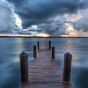 "<h2>The Calm After the Storm</h2> <br/>A few days ago I posted a picture of the storm at the airport here in Palm Beach.  I was contemplating flying into the heart of the storm instead of sitting in a room full of attorneys for the day.  Today I chose the latter and it was about as much fun as it sounds.  It was my first time through this particular experience and it wasn't what I would call a rockin' good time.   I wish I could have said, ""Your honor, the witness (me) is being badgered"" but there was no judge, just a bunch of lawyers quoting rules and regulations I've never heard of.  I think, technically, lawyers have formed a sovereign nation who have created a set of rules that abstract them and all behavior from regular society.  That's another pseudo-sociological concept I am working on, but is a rather empty thing to really think about unless you are on a break in one of those badgering-sessions.  After the session, I headed out to get some pictures around Palm Beach.  I twisted my ankle in an effort to get this one... that dock is even more uneven than it looks!<br/><br/>- Trey Ratcliff<br/><br/><a href=""http://www.stuckincustoms.com/2007/09/24/the-calm-after-the-storm/"" rel=""nofollow"">Click here to read the rest of this post at the Stuck in Customs blog.</a>"
