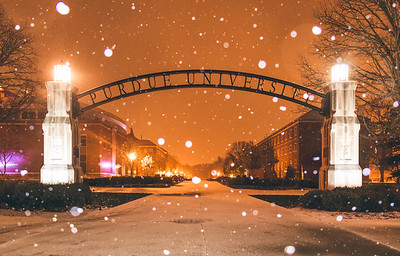 Snow falling around the Gateway to the Future Arch at Purdue University