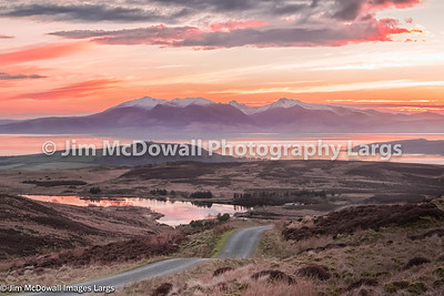 Fairlie Moor Road Reservoir and Arran in the Distance just at Sunset. Arran is in a slight mistly haze.