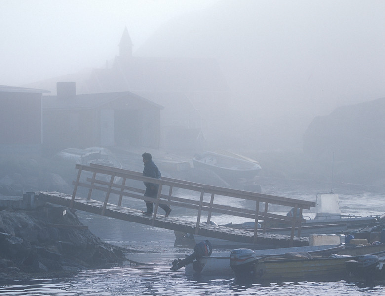 A hunter returns to Aappillatoq, a South Greenland hunting village, in the early morning fog.