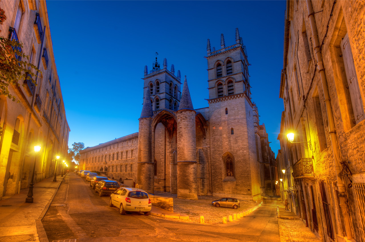 """A Dusk Walk in Montpellier We headed out on an evening walk with our wonderful hosts in Montpellier, France.  They've done a few nice things to the city to minimize car traffic. There is a lot of public transport on light rails, and that tended to keep congestion down.  You don't really realize it until you compare it to someplace like Milan or Daegu, but there just aren't a lot of cars driving around all the most interesting places.  Taking the """"back way"""" to dinner, we stopped at this perfect little intersection so I could take a quick photo.  It was a highly recommended spot by my friend Jacques.  This is the Cathédrale Saint-Pierre de Montpellier an elegant and unique cathedral that has a castle-like feel to the facade.  Since I always get excited when I see a castle, this got a big thumbs up!  - Trey Ratcliff  Read more here at the Stuck in Customs blog."""