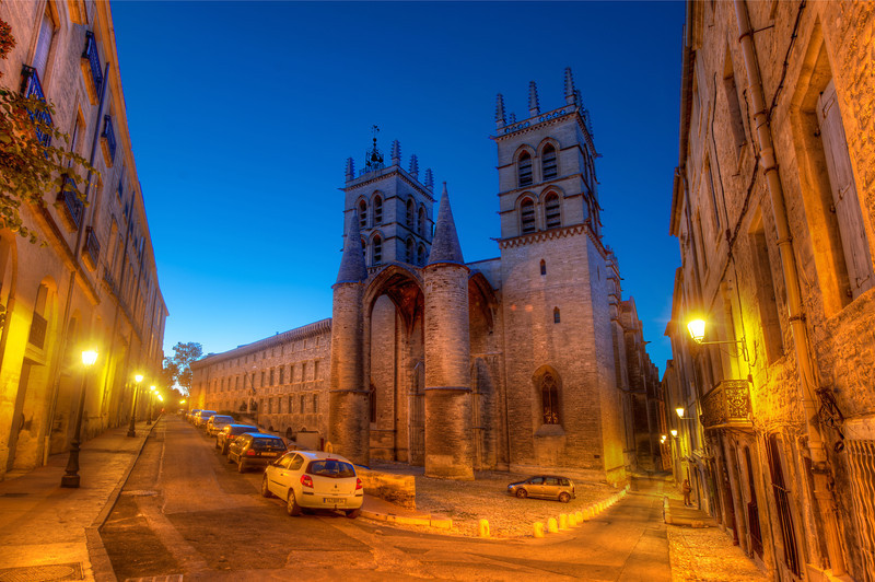 "<h2>A Dusk Walk in Montpellier</h2> We headed out on an evening walk with our wonderful hosts in Montpellier, France.  They've done a few nice things to the city to minimize car traffic. There is a lot of public transport on light rails, and that tended to keep congestion down.  You don't really realize it until you compare it to someplace like Milan or Daegu, but there just aren't a lot of cars driving around all the most interesting places.  Taking the ""back way"" to dinner, we stopped at this perfect little intersection so I could take a quick photo.  It was a highly recommended spot by my friend Jacques.  This is the <em>Cathédrale Saint-Pierre de Montpellier </em>an elegant and unique cathedral that has a castle-like feel to the facade.  Since I always get excited when I see a castle, this got a big thumbs up!  - Trey Ratcliff  Read more <a href=""http://www.stuckincustoms.com/2011/06/19/free-hdr-tutorial/"">here</a> at the Stuck in Customs blog."