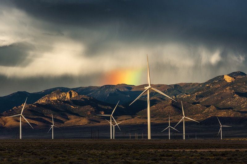 Lingering Rainbow Behind Wind Turbines