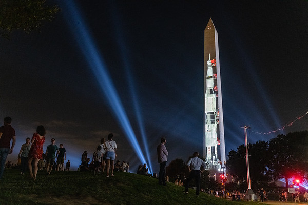 Washington, D.C. -- Visitors watch a projection of Apollo 11 shining on the National Monument before the start of a short showing of the launch on July 19, 2019. The United States celebrated the 50th anniversary of Apollo 11's mission and the first humans to walk on the moon.