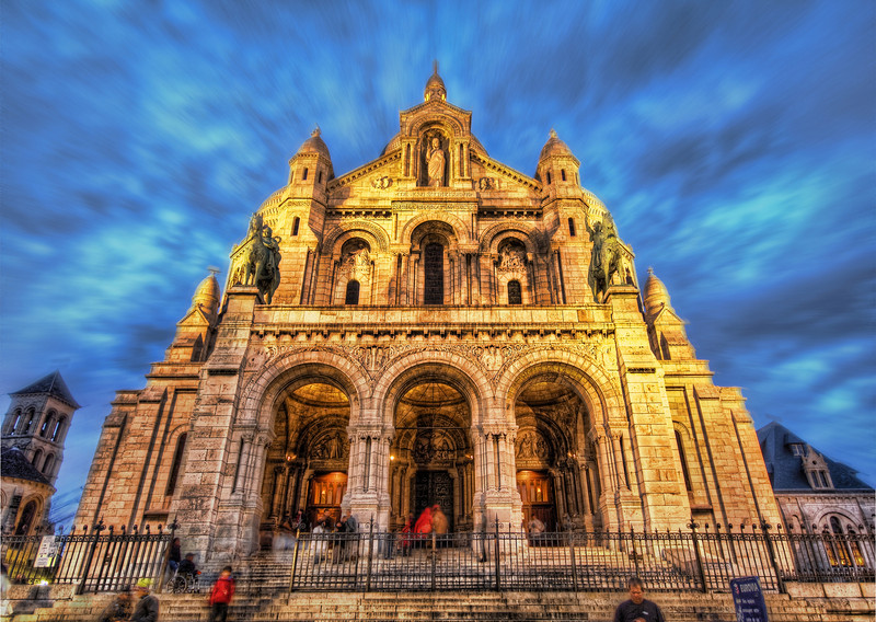 "The Sacred Heart of Paris This is the Sacred Heart Church that sits high on a hill in a very artsy area of Paris. Actually, all of Paris seems artsy to me. I've always wondered what it would be like to be a ""full time artist"" living in Paris. Wouldn't that be just about the coolest thing in the world? Or maybe you would become spoiled in just a short while and take it all for granted. It's very hard to empathize or sympathize with any mystical miserables that might be in that situation.Trey's Tip: I usually take these with a single RAW, but I kind of like the motion in these people... on occasion it seems okay to me, like here.- Trey RatcliffClick here to read the rest of this post at the Stuck in Customs blog."