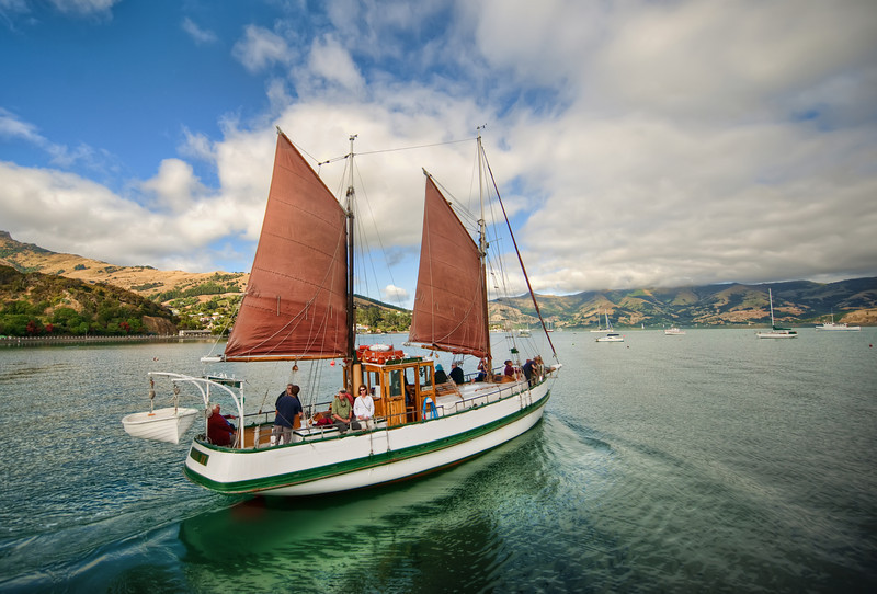 """<h2>Sailing Away to Akaroa</h2> Thanks again for all the recommendations!  So many of you recommended that we visit Akaroa on our visit to New Zealand, and it was a great suggestion.<br><br>You can walk along and see most of the commercial part and the harbor in less than an hour.  One end is a long dock where they launch a few ships per day.  Just as I got out to the end, this sailboat was pulling away from the dock.<br><br>This photo came from a single RAW file.  There was way too much movement to let me do a multiple exposure in this one.<br><br>- Trey Ratcliff<br><br><a href=""""http://www.stuckincustoms.com/2012/02/16/sailing-away-to-akaroa/"""" rel=""""nofollow"""">Click here to read the rest of this post, including info on the podcast, at the Stuck in Customs blog.</a>"""