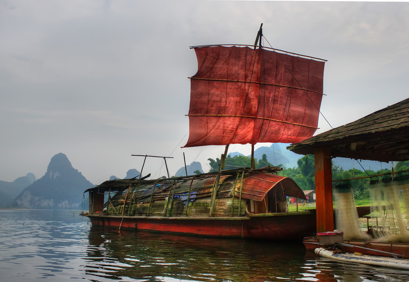 "<h2>Chinese Pirates</h2> <br/>One evening, my boat driver was speeding down the Li River as dusk was approaching.  Every bend held new secrets as we wound our way further from civilization.  I had a bag full of snacks to my left side and my DSLR to my right.  Sitting out on the front of the boat, I had a full view of everything that was coming at me, so it was pretty amazing.<br/><br/>Just before we got to the turn-around spot, we came across this old ship.  Part of me wanted to go inside to explore a little bit... the other part of me was a bit freaked out.  Since I was new to this part of the 'verse, I thought there could be Reavers inside. <br/><br/> - Trey Ratcliff <br/><br/>Read more <a href=""http://www.stuckincustoms.com/2011/05/04/chinese-pirates/"">here</a> at the Stuck in Customs blog."