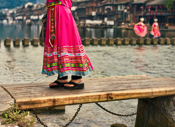 Walking Across the Old Bridge While in China, one of the small towns I visited had several little low walking-bridges across the river.  It was the sort of river that was too shallow for boats, but good for fishing and washing clothes.  This one was in a residential and commercial area.  Many of the women wore colorful dresses and walked back and forth across... it all seemed very nice and peaceful so I grabbed an image.  - Trey Ratcliff  Read more here at the Stuck in Customs blog.