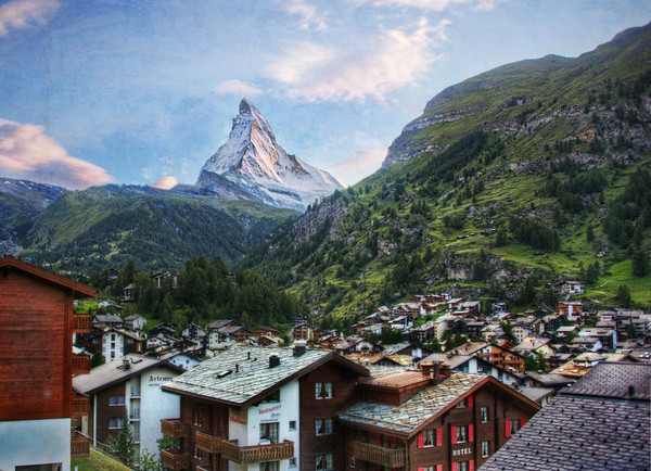 The Matterhorn over the VillageWhile taking the train up a nearby mountain in the town of Zermatt, there is one quick moment when you get this perfect view of the village and the Matterhorn together.I think I really liked this place because I remember riding the Matterhorn with my dad when I was a kid, and my child-mind could not conceive of an actual Matterhorn!- Trey RatcliffClick here to read the entire post at the Stuck in Customs blog.