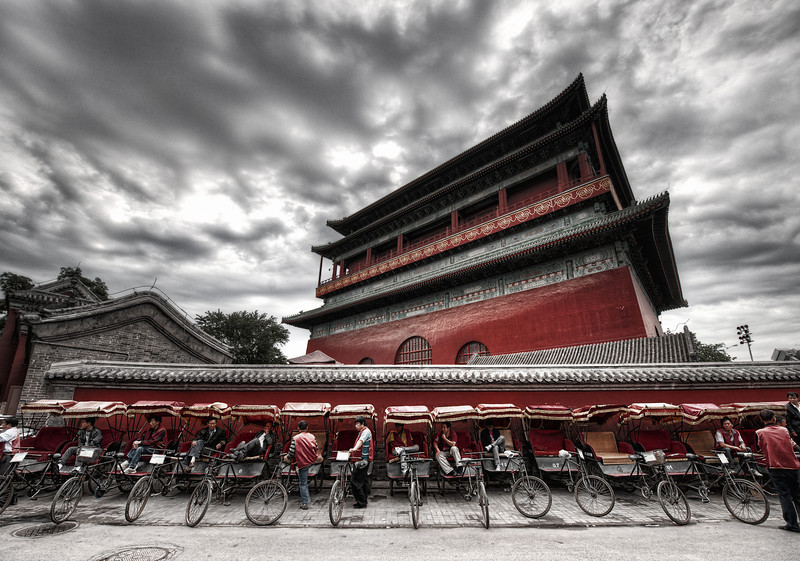 """<h2>Rickshaws at the Drum Tower</h2> <br/>I've visited Gǔlóumany times and never taken a photo. I just couldn't figure one out.<br/><br/>And then, this most recent trip, I walked around the tower several times until I finally got an idea.<br/><br/>This is the giant drum tower built about a thousand years ago by Kublai Khan. An enormous drum rests in front, and it was beat rhythmically to announce meetings. The temple sits in the Inner City to the north of Di'anmen Street.<br/><br/>- Trey Ratcliff<br/><br/>Read more, including a preview of an exciting announcement, <a href=""""http://www.stuckincustoms.com/2011/10/21/rickshaws-at-the-drum-tower/"""">here</a> at the Stuck in Customs blog."""