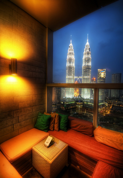 """<h2>An Open Air Lounge in Kuala Lumpur</h2> <br/>Isn't this place awesome? It's a bar on top of a roof of the Trader's Hotel in Kuala Lumpur. It looks out across the new skyline at the Petronas Towers. Malaysia is a pretty hot and humid country, so sometimes it's not quite so comfy to sit outside. I don't like to sit outside in muggy conditions… I just don't. I remember that I played indoor soccer there in Kuala Lumpur on another night and it was one of my top 10 sweaty nights. Afterward, the only way to cool off was to drink about 128 oz of iced carrot-milk. That doesn't sound very good, but it is.<br/><br/>- Trey Ratcliff<br/><br/><a href=""""http://www.stuckincustoms.com/2009/09/25/an-open-air-lounge-in-kuala-lumpur/"""" rel=""""nofollow"""">Click here to read the rest of this post at the Stuck in Customs blog.</a>"""