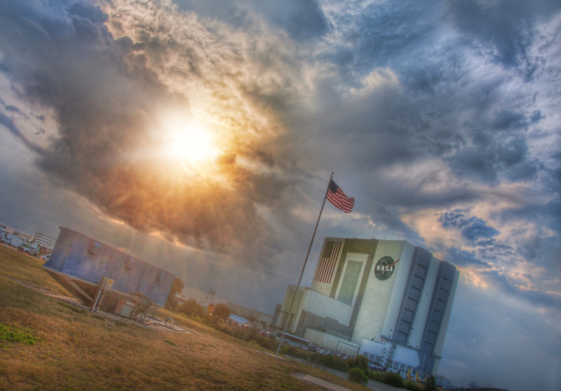 "<h2>Sun Busting Through Stormclouds at NASA</h2> I was in the Tweetup tent doing something terribly important but completely inscrutable when Stu Maschwitz came in and told me that the storm clouds were breaking upon our shores.  So I got my little rig and went outside to see the matter.  We get these kind of huge powerful summer clouds in Texas too.  The kind that roll in on a too-hot day and you have a feeling that something powerful is a-comin'.  You tie down the cows and take the favorite sheep down to the basement because it's gonna be a long night...  The sun darted in and out of the clouds, and I grabbed it just as it peeked through a small hole it tore in the thunderhead.  - Trey Ratcliff  Read more <a href=""http://www.stuckincustoms.com/2011/07/06/sun-busting-through-stormclouds-at-nasa/"">here</a> at the Stuck in Customs blog."