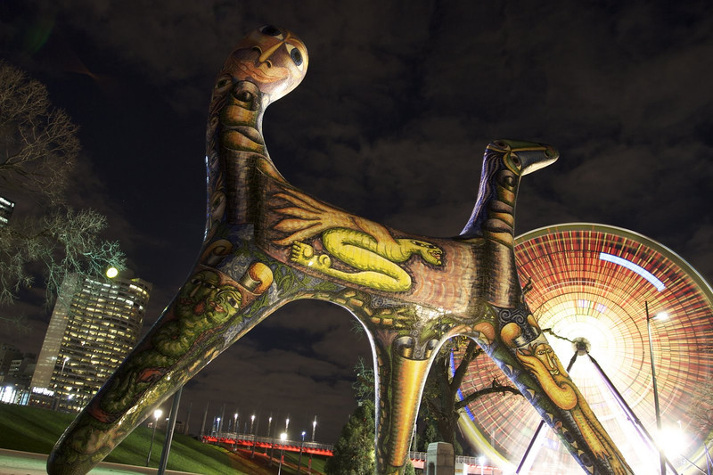 A painted sculpture, with a ferris wheel in the background taken at night. This was taken in Melbourne, Australia on the banks of the Yarra.  At the time it was pretty slow, and no one was on the ride, yet the wheel kept spinning.