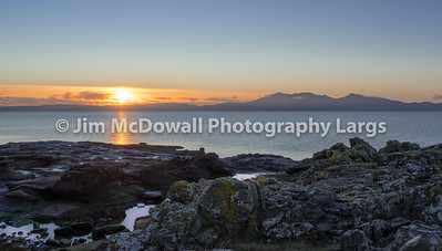 Sun Going Down Behind the Isle of Arran from Portencross North Ayrshire on a Cold Bright Christmas Eve in Scotland.