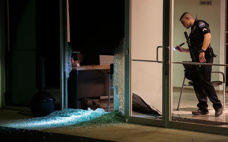 Nadav Soroker/Times-Georgian<br /> <br /> Corporal Josh Perry shines his light through a broken plate-glass pane which an unidentified man broke with a brake rotor at the John Thornton GMC dealership, on Friday, March 22, 2019. Security cameras at the dealership showed that the man left before police arrived.