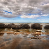 "<h2>The Mysterious Moeraki Boulders</h2> <br/>These are some of the most mysterious and alien structures I have ever seen! <br/><br/>Yesterday I remarked that I had a major in computer science.  Well, for a short time, I had a double-major in comp sci and Geophysics.  I got pretty deep into it until I had a fight with a Geology teacher over an intellectual matter (he was wrong and still is), and I dropped that half of the major.  Anyway, it never dulled my interest in rocks and Earth science.  So, when I saw these strange round rocks for the first time, I was extra-fascinated.  Not that I had any idea what they were.  My years of geology training did me no good at all...  I think it was even more frustrating because I knew all the things they <em>could not</em> be.  The remaining possibilities just seemed off-the-chart impossible.<br/><br/>And worse, I didn't have a mobile connection to Wikipedia to help me figure it all out with my iPhone-tricorder! <br/><br/>After I got back, I was able to figure out a bit more of the arcane science around it all.  Even more interesting, I read that 12 miles south of this spot is another are called the ""Katki Boulders"".  They contain the bones of mosasaurs and plesiosaurs.  Cool!<br/><br/>- Trey Ratcliff<br/><br/><a href=""http://www.stuckincustoms.com/2010/05/20/moerakiboulders/"" rel=""nofollow"">Click here to read the rest of this post at the Stuck in Customs blog.</a>"