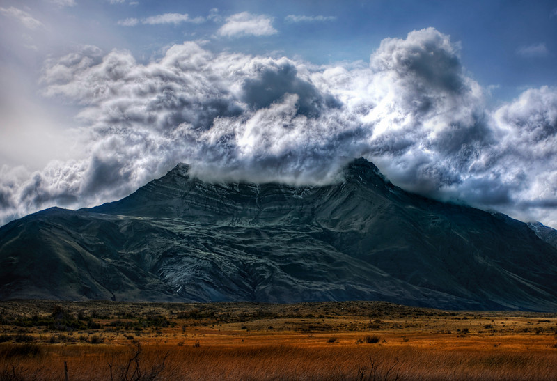 """<h2>The Violent Volcano</h2> <br/>I thought this mountain and cloud formation was too perfect to ignore.  Clouds always do strange things when they pass over mountains, but this one seemed particularly violent and unexpected.<br/><br/>This is not actually a volcano.  it's just a regular old mountain in the Andes that had a nice little volcanic shape.  I skirted around it for a while (skirting is quite a trek at this radius), until the angle seemed about right... although I had to skirt fast before the clouds changed.  I have always wanted to take a photo of a volcano that is erupting.  I climbed up part of a volcano that was erupting in Costa Rica, and you could see the red rocks, but I got absolutely zero good shots.  Oh well... some day!<br/><br/>- Trey Ratcliff<br/><br/><a href=""""http://www.stuckincustoms.com/2009/05/16/the-violent-volcano/"""" rel=""""nofollow"""">Click here to read the rest of this post at the Stuck in Customs blog.</a>"""