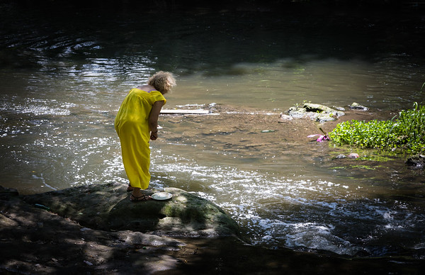 Woman in a long yellow dress by a river